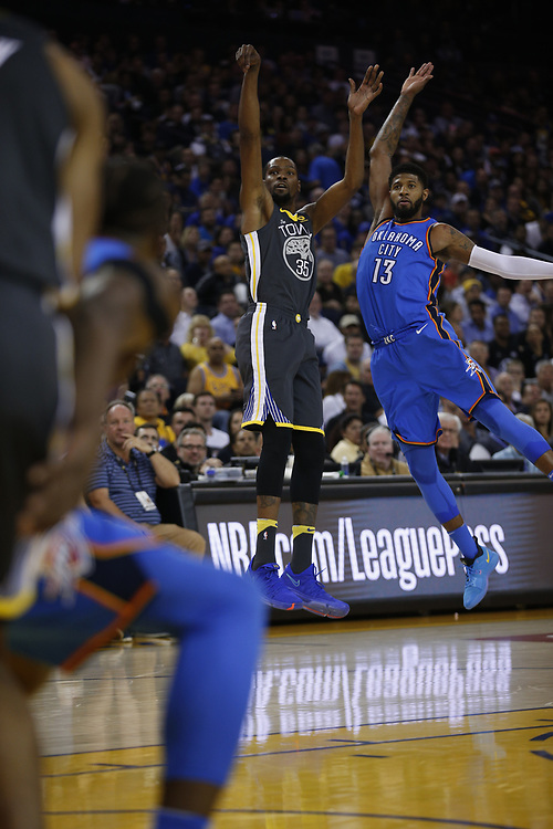Golden State Warriors forward Kevin Durant (35) shoots against Oklahoma City Thunder forward Paul George (13) during the first half of an NBA game between the Warriors and Oklahoma City Thunder at Oracle Arena, Tuesday, Feb. 6, 2018, in Oakland, Calif.