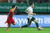 Gareth Bale, right, of Wales national football team kicks the ball to make a pass against Wei Shihao of Chinese national men's football team in the semi-final match during the 2018 Gree China Cup International Football Championship in Nanning city, south China's Guangxi Zhuang Autonomous Region, 22 March 2018.