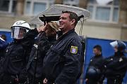Frankfurt am Main | 20 Jun 2015<br /> <br /> Kundgebung der islamfeindlichen Gruppe &quot;Widerstand Ost West&quot; (WOW) um Ester Seitz, die Rechtspopulisten, rechte Hooligans und Neonazis vereint, auf dem Rossmarkt.<br /> Hier: Polizisten sch&uuml;tzen sich mit ihren Schilden vor dem Regen.<br /> <br /> Photo &copy; peter-juelich.com