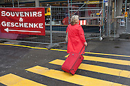 Europe, Germany, Cologne,  woman is crossing a crosswalk near the cathedral.<br />