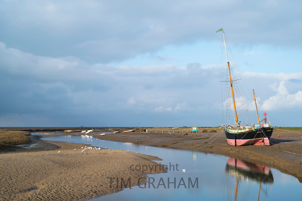 Yacht moored on mud at Blakeney Estuary in Norfolk, UK