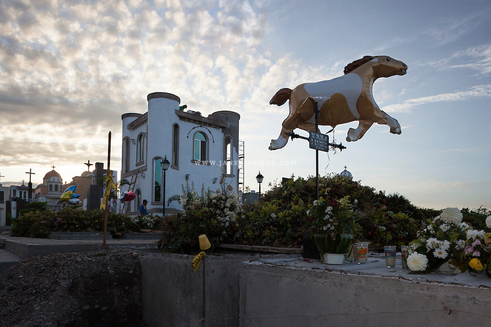 A horse shaped balloon floats at sunset, marking the graves of the recently buried inside Jardines del Humaya in Culiacán, Sinaloa, one of the most notorious cemeteries in Mexico. Culiacán has long been a center of the country's drug trade, and families often erect elaborate mausoleums for gang members killed in the drug battles.