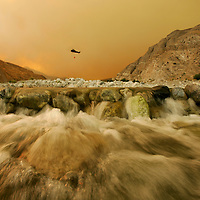 Crystal Chatham/The Desert Sun<br /> <br /> 07/15/2006 -- A firefighting helicopter picks up water from the Whitewater Dip Site on Saturday evening as smoke billows behind a creek and Whitewater Canyon. Three helicopters rotated through the site throughout the day.