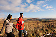 Young Asian man and woman hold hands walking through the Moffat Hills with long grass and snowy hills in the background on a sunny day.