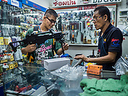 29 SEPTEMBER 2015 - BANGKOK, THAILAND:  A high school student buys a toy assault rifle in the Saphan Lek market. Street vendors and illegal market vendors in the Saphan Lek area will be removed in the next two weeks as a part of an urban renewal project coordinated by the Bangkok Metropolitan Administration. About 500 vendors along Damrongsathit Bridge, popularly known as Saphan Lek, have 15 days to relocate. Vendors who don't move will be evicted. Saphan Lek is just one of several markets and street vending areas being closed in Bangkok this year. The market is known for toy and replica guns, bootleg and pirated DVDs and CDs and electronic toys.   PHOTO BY JACK KURTZ