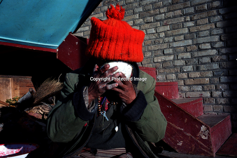 """MEILI MOUNTAIN, DECEMBER 17, 2000: a Tibetan nomad eats Tsampa at Feilai monastery near Mt. Meili in the morning in deqin county, Yunnan province , December 17, 2000..Mt. Meili is the highest peak in Yunnan province and according to supporters from Deqin county, it's a """"proof"""" that the 'real"""" Shangri-La is located in deqin county. The fictuous Mt. Karakal which is described in James Hilton's Lost Horizon, alledgedly is modelled on Mt. Meili in Yunnan province.."""