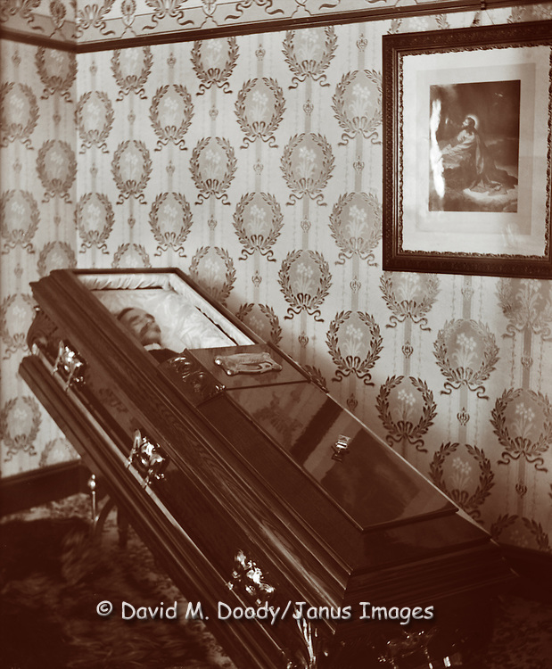 Vintage Photo: Dead man in casket,  1908 a picture of Jesus hangs over the coffin. Postmortem
