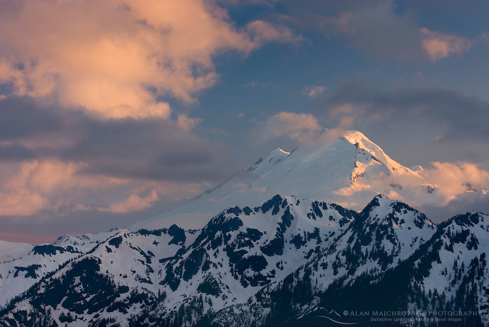 Mount Baker (elevation 10,778 feet (3,285 m) seen through clearing storm clouds at sunset, North Cascades Washington USA