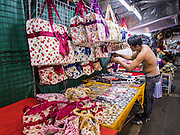 23 AUGUST 2014 - BANGKOK, THAILAND:        A Thai man sets up his stand selling bags at a night sidewalk market on Sukhumvit Road near Soi 5 in the Nana section of Bangkok. The Thai military junta, formally called the National Council for Peace and Order (NCPO), has ordered street vendors off of the sidewalks in an effort to bring order to Bangkok's chaotic sidewalks. Vendors have complained that the new regulations are hurting them economically but largely complied with the military orders.    PHOTO BY JACK KURTZ