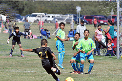 A young player from Cualcoman, a coed Salinas Soccer League team, begins his run at a perfectly curved free kick, arcing over both defenders and the goalkeeper from Atlas Junior to score a goal. Sundays at the Constitution Soccer Complex in Salinas are typically packed with players, parents, friends, and vendors watching games and cheering on their favorites.