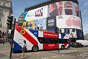 A tour bus with The Original Tour drives below advertising hoardings in Piccadilly Circus Square, on 7th July 2017, in central London.