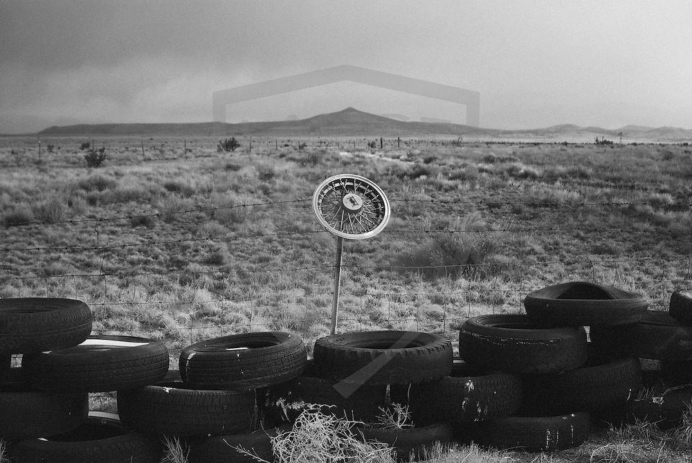 a hubcap on a barbed wire fence and old tires with the southwest desert landscape, santa fe, new mexico