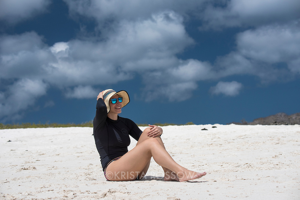 Lindblad Expeditions guest staff, Carolyn DeMonaco, sits on the beach at Gardner Bay, one of the most beautiful beaches in the world, on Espanola Island in the Galapagos Islands of Ecuador.