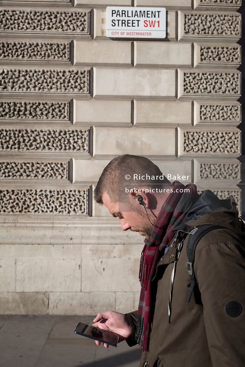 At a time when the UK government is embroiled in a controversial decision to allow Chinese phone technology manufacturer, Huawei access to a future 5G environment, a man walks and looks at his phone beneath the signpost for Parliament Street SW1, Westminster, on 29th January 2020, in London, England.