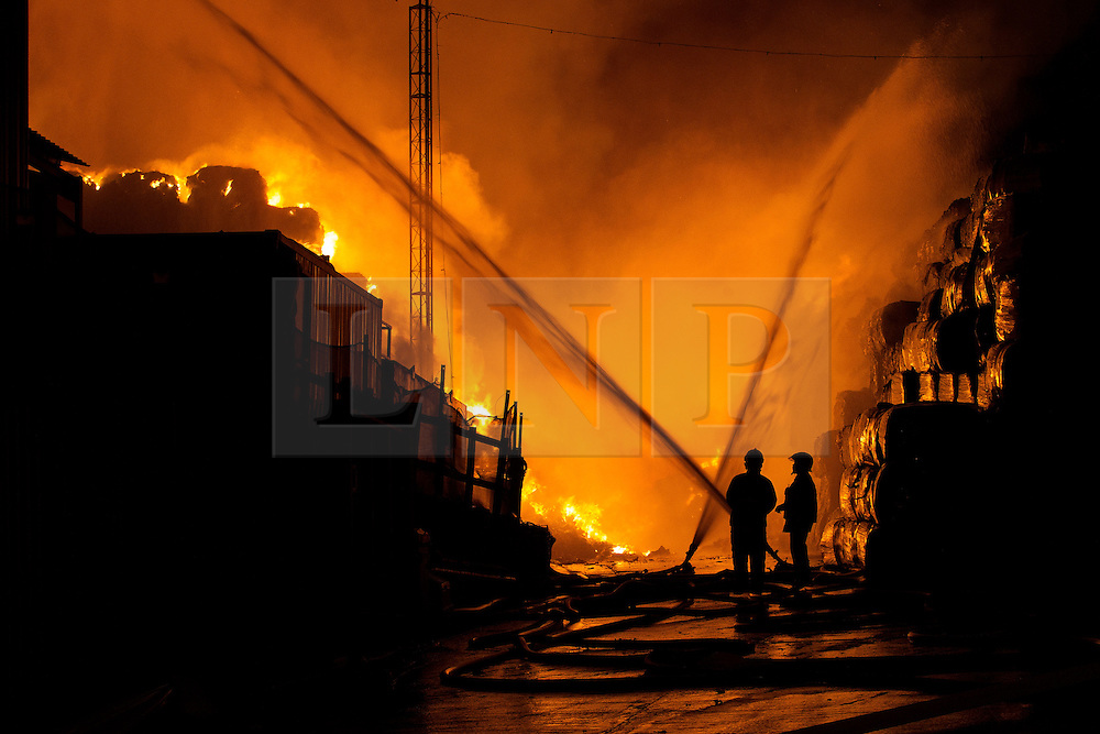 © Licensed to London News Pictures . 21/08/2013 . Stockport , UK . Firefighters tackle the intense blaze at the J25 Recycling Centre in Bredbury , Stockport this morning (Wednesday 21st August 2013) where a building and bales of recyclable material are alight . The fire , which started late last night (20th August) is being tackled by more than 50 fire crew . The site , which is adjacent to a branch of Morrisons Supermarket and McDonalds , is off Junction 25 of the M60 motorway , exits for which are closed in both directions . Photo credit : Joel Goodman/LNP