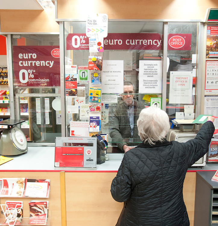 Pictured is Moulton Post Office postmaster Gary Mound serving customer Jenny Armitage<br /> <br /> Moulton Post Office, Spalding, Lincolnshire.<br /> Community Funding.<br /> <br /> Date: December 2, 2014