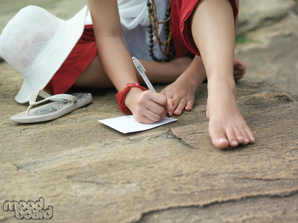 Young woman sitting on rock writing low section