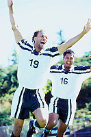 Teammates run and celebrate after a goal in a soccer match.