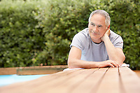 Middle-aged man sitting at table by pool surface view