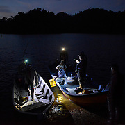 Honey hunters ride boats from their camping site to the place that they will harvest the honey during twilight of February 28, 2016.