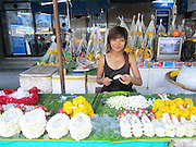 Woman arranging flowers for a phuang malai floral garland at the Pak Khlong Talat flower market in Bangkok, Thailand. Graceful!