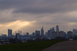 Primrose Hill, London, February 15th 2015. A shaft of sunlight illuminates Docklands on a chilly early morning on Primrose Hill, overlooking London&rsquo;s skyline.<br /> ///FOR LICENCING CONTACT: paul@pauldaveycreative.co.uk TEL:+44 (0) 7966 016 296 or +44 (0) 20 8969 6875. &copy;2015 Paul R Davey. All rights reserved.