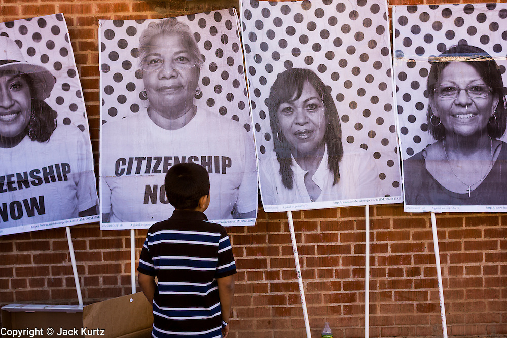 05 OCTOBER 2013 - PHOENIX, ARIZONA:   A boy looks at placards of immigrants an immigration march in Phoenix Saturday. More than 1,000 people marched through downtown Phoenix Saturday to demonstrate for the DREAM Act and immigration reform. It was a part of the National Day of Dignity and Respect organized by the Action Network.    PHOTO BY JACK KURTZ