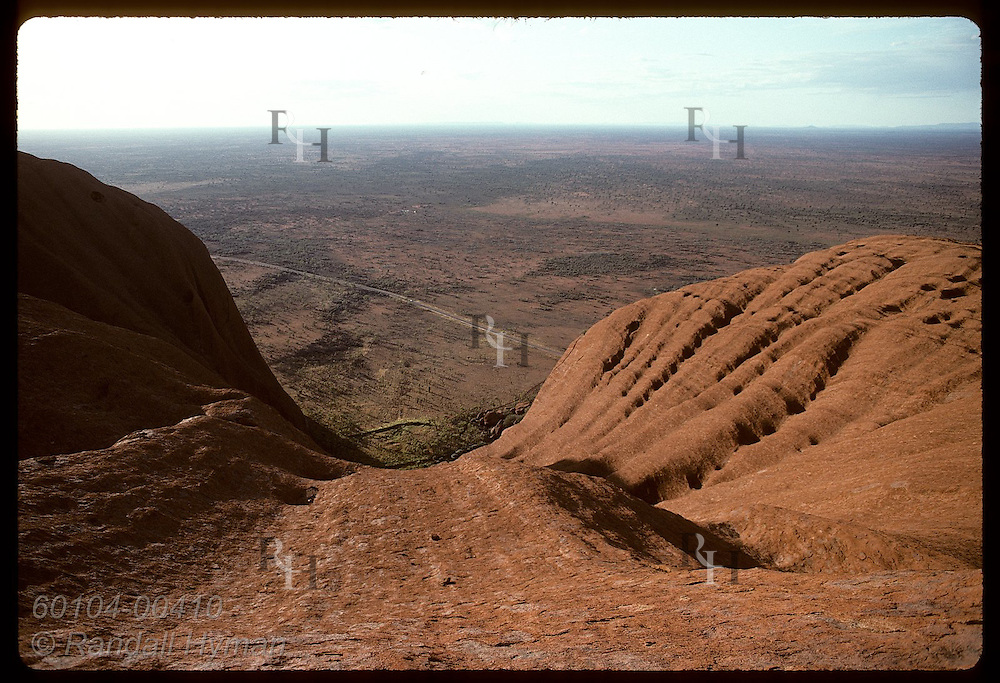 Seen from atop Ayers Rock on summer morn, steep sandstone walls sweep 348 meters down to desert. Australia