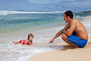 A father pulls his little girl on a boogie board on the beach in Hawaii
