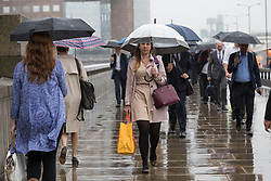 © Licensed to London News Pictures. 09/08/2017. LONDON, UK.  Commuters crossing London Bridge are caught in heavy rain and wet weather this morning. Rain is forecast to fall across areas of London and the south east of England today.  Photo credit: Vickie Flores/LNP