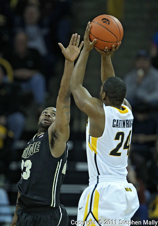 December 28, 2011: Purdue Boilermakers guard Lewis Jackson (23) tries to block a shot by Iowa Hawkeyes guard Bryce Cartwright (24) during the NCAA basketball game between the Purdue Boilermakers and the Iowa Hawkeyes at Carver-Hawkeye Arena in Iowa City, Iowa on Wednesday, December 28, 2011. Purdue defeated Iowa 79-76.