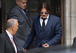 © Licensed to London News Pictures. 07/07/2020. London, UK. US actor Johnny Depp looks down at a half rolled cigarette as he leaves The High Court in Central London. Johnny Depp's libel trial against The Sun newspaper is due to take place over the next three weeks over allegations he was violent and abusive towards his ex-wife Amber Heard. Photo credit: Peter Macdiarmid/LNP
