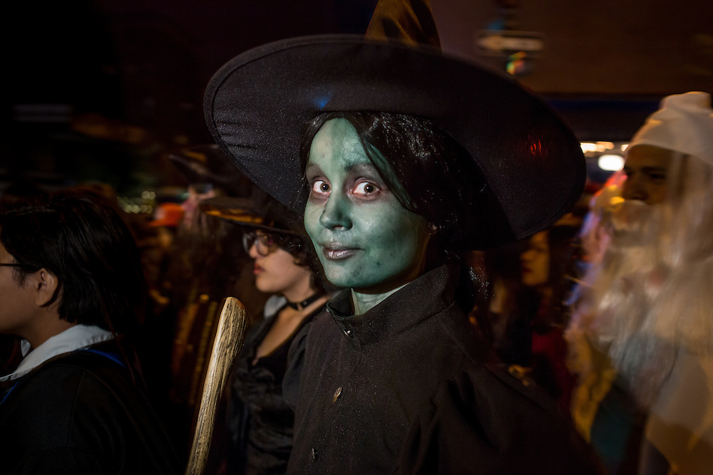 New York, NY - 31 October 2015. A woman with green face makeup and a witch's hat made up to look like Elphaba, the wicked witch in The Wiz in the Greenwich Village Halloween Parade.