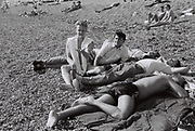 Friends lying on Brighton Beach, UK, 1985