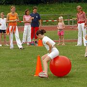 NLD/Huizen/20050715 - Sportdag Koninging Wilhelminaschool Huizen, kinderen op skippyballen doen een wedstrijdje