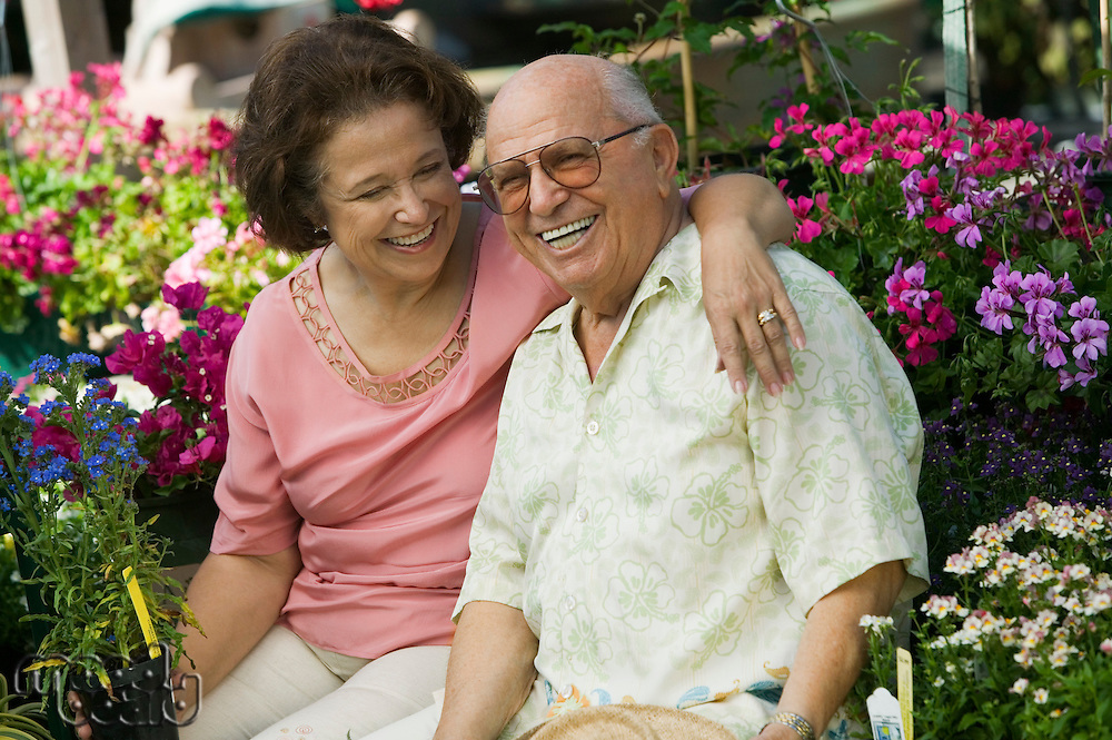 Senior Couple sitting among flowers at plant nursery portrait