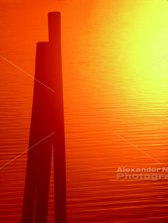 USA, Newport, RI - Silhouette of three pilings, abstracted by the deep orange sun and the rippling water.