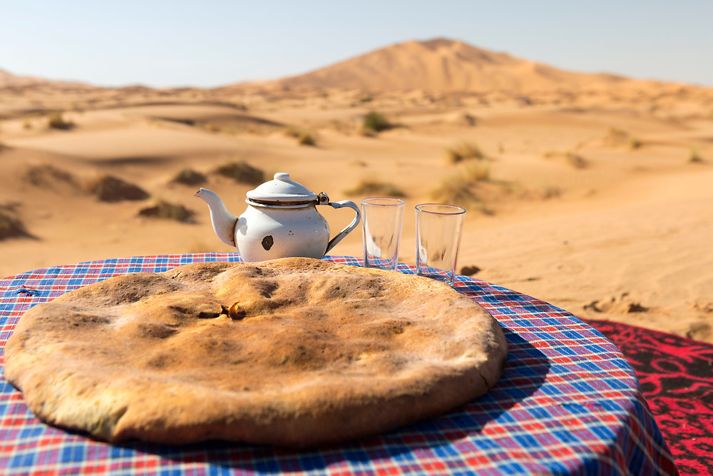 The limited resources of the Sahara's arid terrains means food needs to be easy to prepare. When a mud oven is not available, nomads use more rustic methods for cooking the stuffed bread by working with the only elements and resources available, such as fire and the sand, Merzouga, Southern Morocco, 2017-12-15.<br />