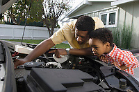 Father and son (5-6) repairing car's engine