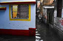 A boy watches from his window over the flooded alley in front of his house.