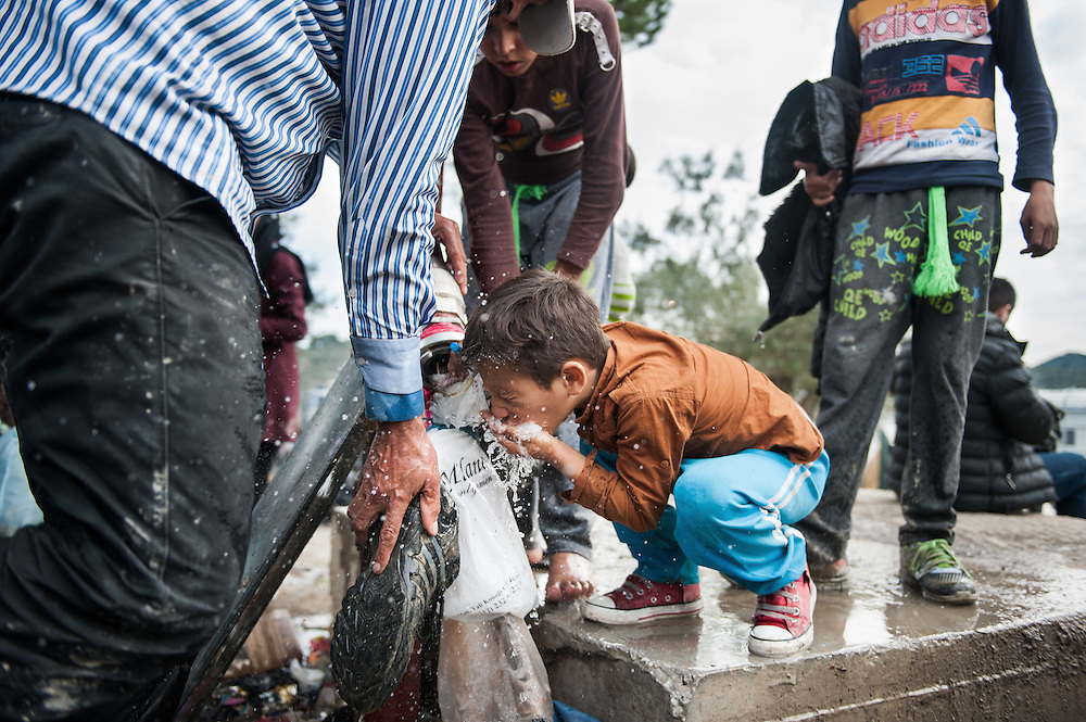 A boy drinks water from a water tap in Moria camp , Lesvos, Greece.