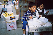 01 DECEMBER 1988   - HONG KONG: Children snack in an alley in Hong Kong.   PHOTO © JACK KURTZ  children  family  lifestyle  poverty