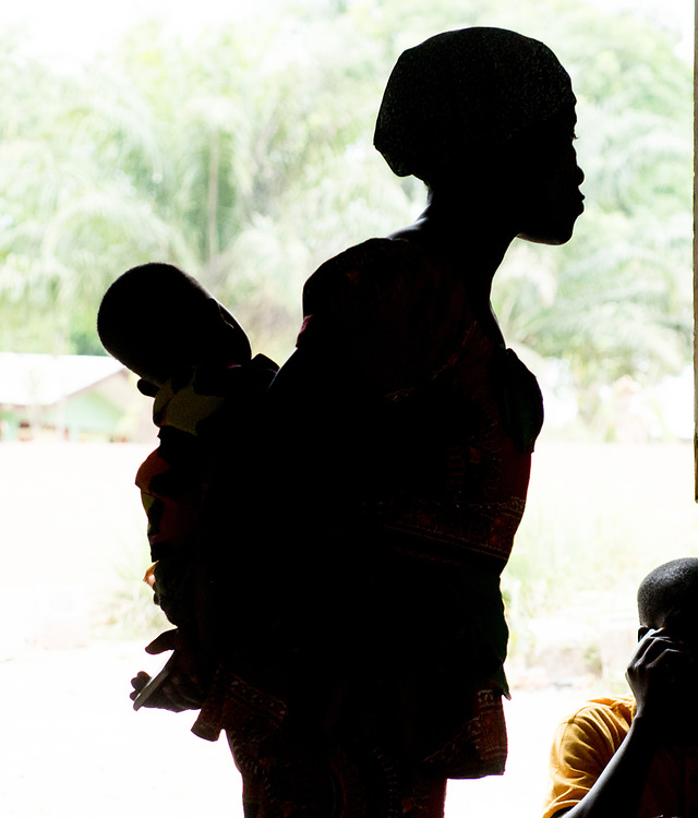 A silhouetted woman holds a child at a church service in Ganta, Liberia