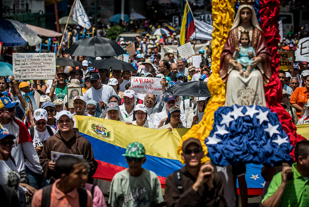 """CARACAS, VENEZUELA - MAY 27, 2017: A nun holds up a sign that says, in Spanish, """"The Truth is Always Persecuted"""" - quote by the famous Archbishop, Óscar Romero of El Salvador who spoke out in defense of human rights and was assassinated because of it.  Priests, nuns and hundreds of other Catholics participate in a peaceful protest against government violence in Caracas. The streets of Caracas and other cities across Venezuela have been filled with tens of thousands of demonstrators for nearly 100 days of massive protests, held since April 1st. Protesters are enraged at the government for becoming an increasingly repressive, authoritarian regime that has delayed elections, used armed government loyalist to threaten dissidents, called for the Constitution to be re-written to favor them, jailed and tortured protesters and members of the political opposition, and whose corruption and failed economic policy has caused the current economic crisis that has led to widespread food and medicine shortages across the country.  Independent local media report nearly 100 people have been killed during protests and protest-related riots and looting.  The government currently only officially reports 75 deaths.  Over 2,000 people have been injured, and over 3,000 protesters have been detained by authorities.  PHOTO: Meridith Kohut"""
