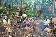 Batwa tribes people waiting for the fermenting of the plantains to make plantain wine and whiskey on the edge of Bwindi Impenetrable Forest, Uganda.