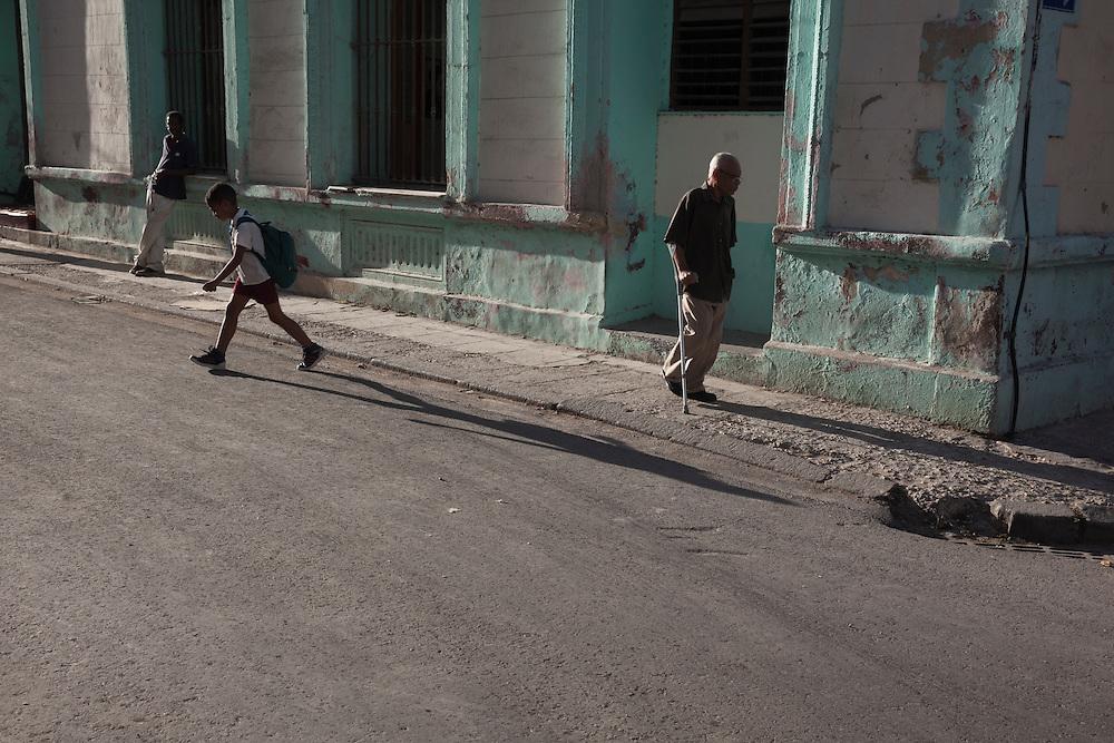 Three generations wall in different directions on a street of Centro Habana, in Havana, Cuba. <br /> <br /> Tres generaciones caminan en distintas direcciones en un cruce de una calle de Centro Habana.