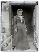glass plate of woman standing in front of door opening of houseboat Paris 1900s