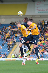 Southend United's Barry Corr heads from Oxford United's Michael Raynes and Oxford United's Asa Hall - Photo mandatory by-line: Nigel Pitts-Drake/JMP - Tel: Mobile: 07966 386802 05/10/2013 - SPORT - FOOTBALL - Kassam Stadium - Oxford - Oxford United v Southend United - Sky Bet League 2
