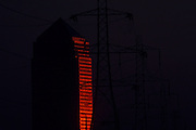 Red glowing sun reflected off the glossy facade of Canary Wharf tower next to electricity pylons.