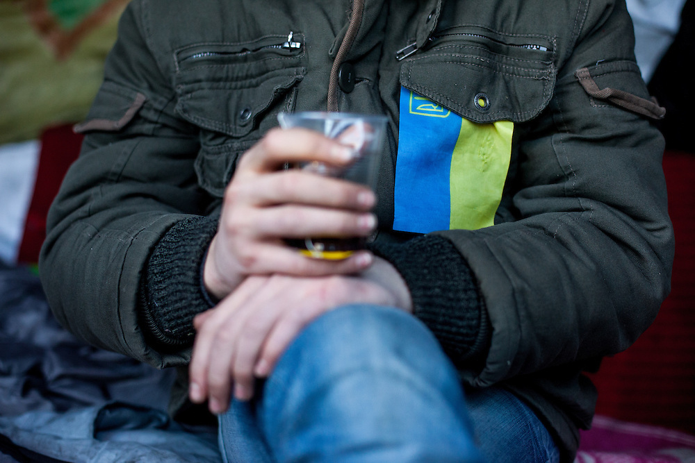 "A young man with the ukrainien flag on his jacket drinking tee at the barrikades which are blockading a building supplies store named ""Epicenter"" in the city of Lviv, Ukraine."